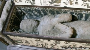 "The mummy as found within its sarcophagus. ""Death, eternal punishment, for, anyone, who, opens, this, casket."""